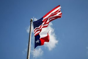 A flag of Texas on a pole next to a US flag.