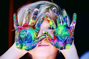 A child holding her hands up with paint on them.