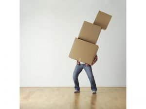 A man carrying a stack of boxes.