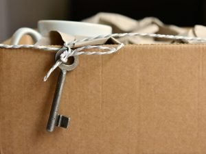 A cardboard box with a key on a ribbon, representing safety.