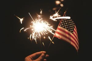 A sparkler and a flag of the US