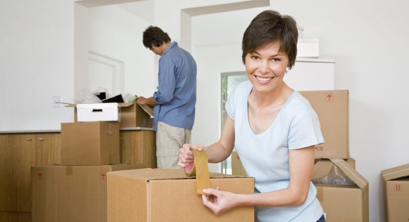 Woman taping moving boxes