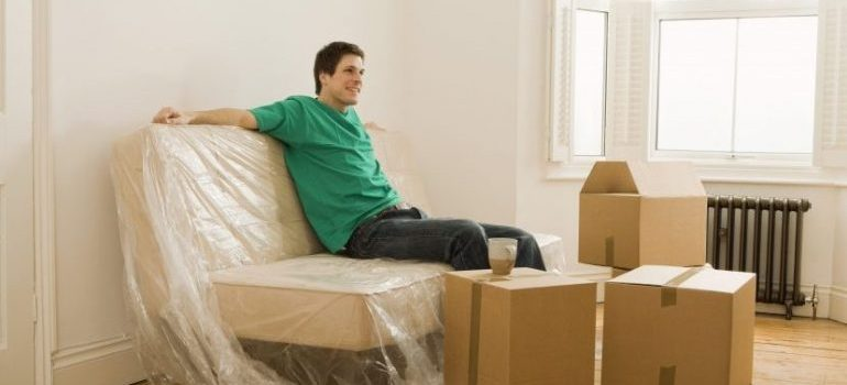 Man relaxing in new home after the work of our movers Plano TX