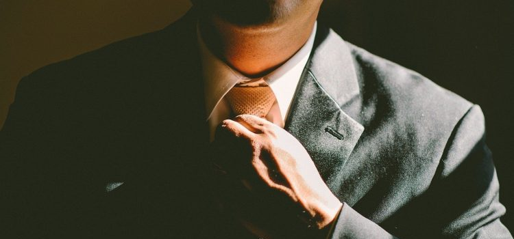 A man in a suit fixing his tie.