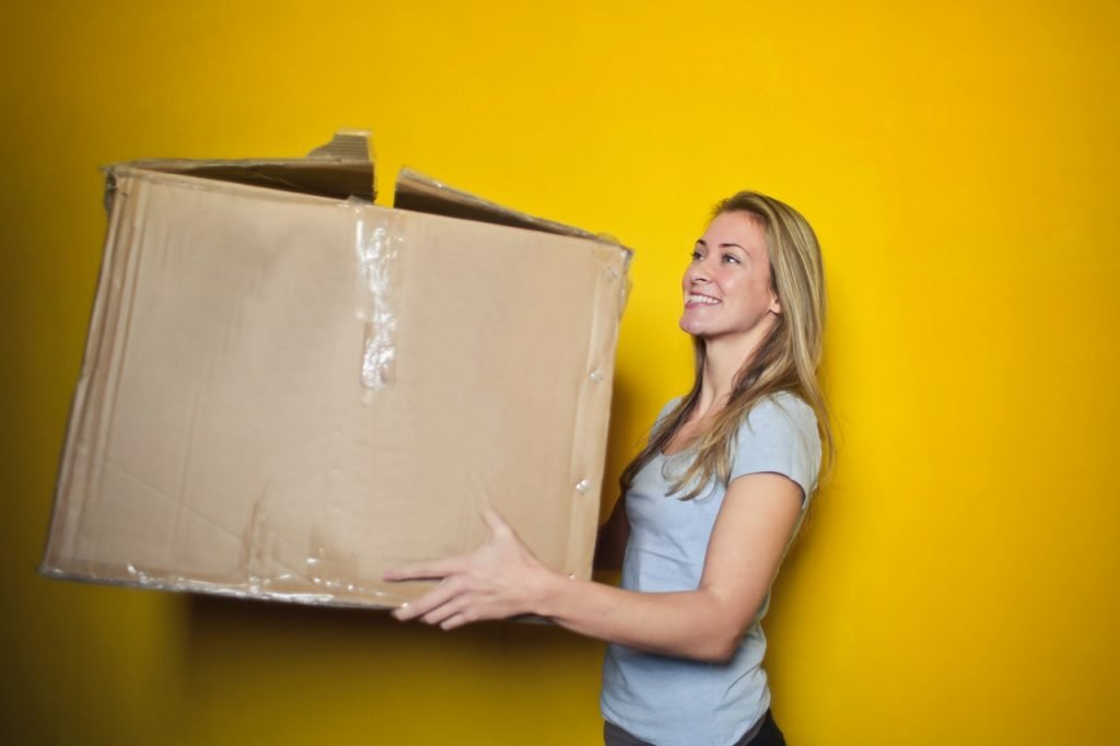 A woman carrying a damaged box