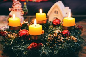 Four lighted candles with some evergreens around them