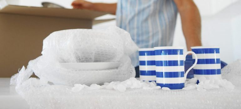Mugs and plates wrapped in bubble wrap - prepare collectibles for moving