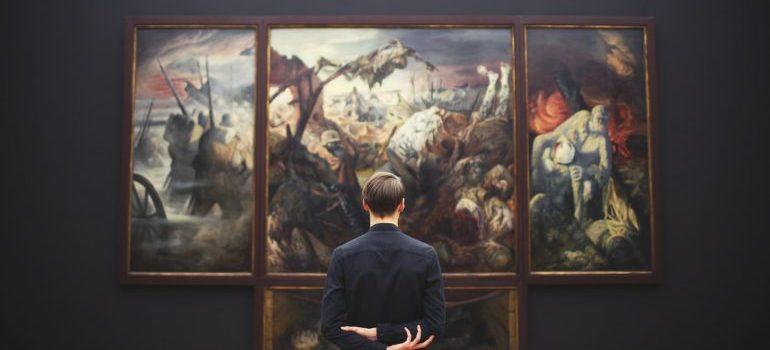Man in black shirt looking at paintings - prepare your art collection for moving