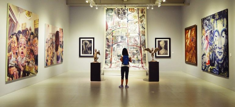 A girl with a blue backpack looking at paintings - Tips for moving your valuables