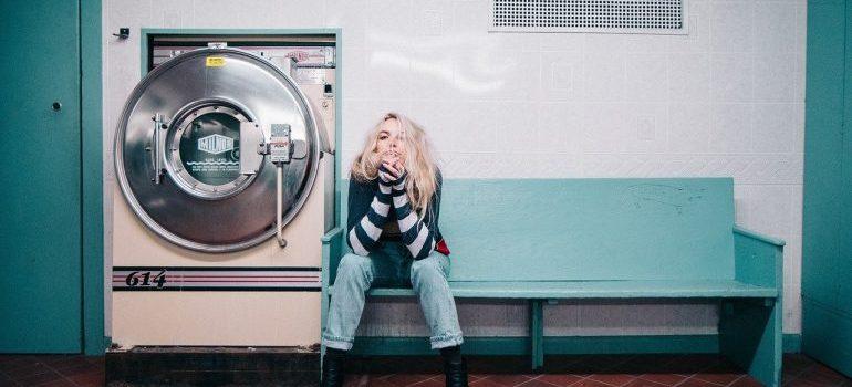 Woman sitting next to the washing machine - Lowering utility bills