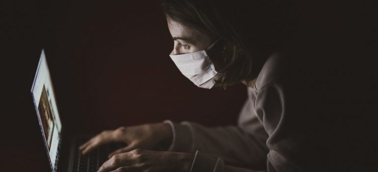 Person wearing face mask looking at laptop - plan your move to Plano in 2020