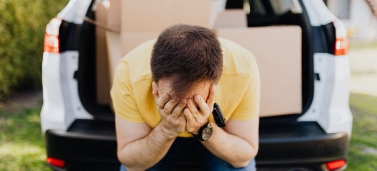 A man covering his face with hands in the moving van