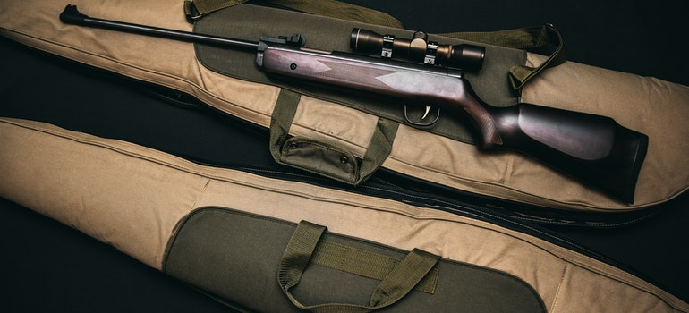 A rifle with a gig bag - use bags and cases for safely storing firearms