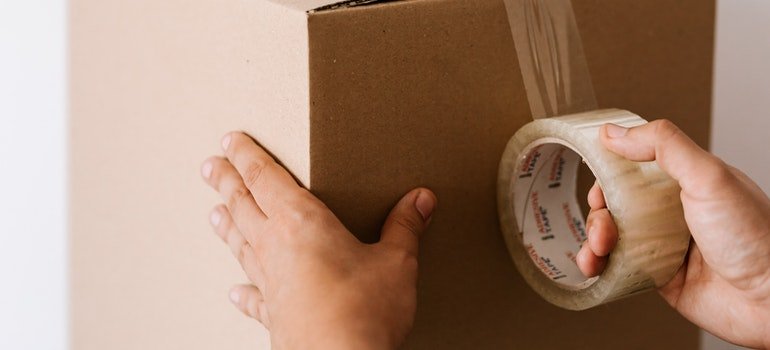 A person packing a box