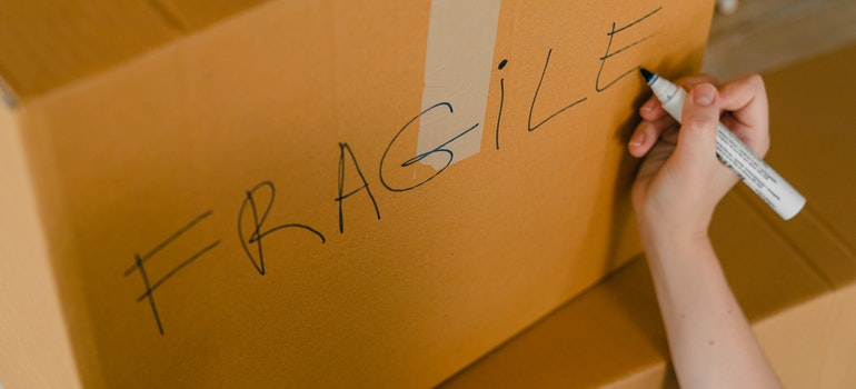 Person labeling a box to avoid common DIY moving mistakes