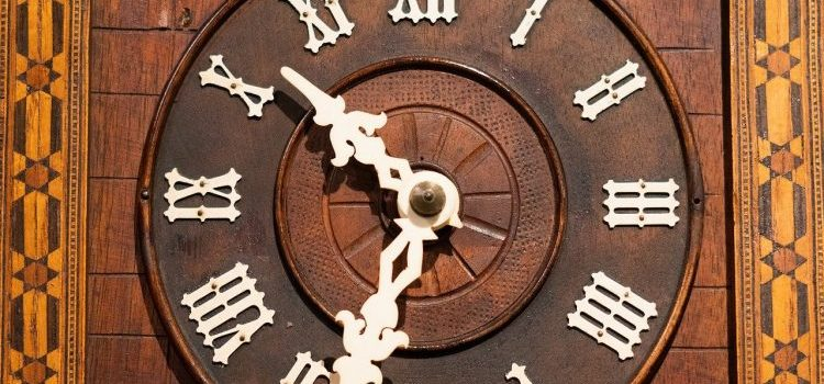 clock hands on a brown wooden grandfather clock
