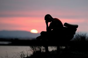 A depressed man sitting by the water at sunset.