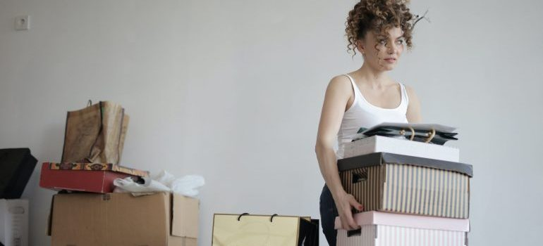 A woman carries boxes.