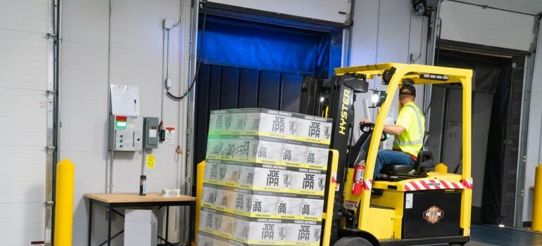 A man on a yellow forklift in a storage unit
