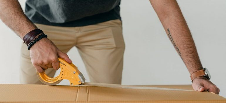 A man packing a cardboard box.