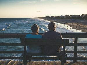 The couple is sitting in wooden bench in one of the best places in Texas to retire
