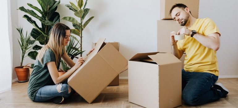 a couple packing and taping cardboard boxes in their living room before combining two homes into one