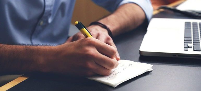 a man writing on paper - move your business to Fort Worth