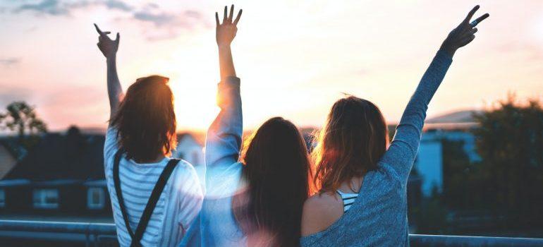 three women raising hands - get packing supplies for free